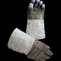 These Extra-Vehicular (EV) gloves were made for and worn by astronaut Neil Armstrong, Commander of the Apollo 11 mission in July, 1969.  The gloves were constructed of an outer shell of Chromel-R fabric with thermal insulation to provide protection while handling extremely hot or cold objects. The blue fingertips were made of silicone rubber to provide sensitivity. The inner glove was of a rubber/neoprene compound, into which the restraint system was integrated, and they attached to the spacesuit using the same mechanism as the intra-vehicular gloves.  Transferred to the National Air and Space Museum from NASA in 1971.  Transferred from NASA, Johnson Space Center
