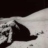 "US$ 1,500 - 2,000 THREE LARGE Photos—making a lunar surface PAN of ""Split Rock"" during EVA 3 on Apollo 17 APOLLO 17 PANORAMIC VIEWS OF TRACY'S BOULDER—SITE BECOMES THE SUBJECT OF AN ALAN BEAN SPACE PAINTING  Three large black and white photographs, each 11 x 14 inches. These combined overlapping photographs create an image approximately 11 x 32 inches. The mosaic is comprised of Apollo 17 lunar surface images AS17-140-21492, 21495, and 21497.  Astronaut Gene Cernan recorded these panoramic views of then called ""Split Rock"" while at Station Stop 6 during Apollo 17's third lunar surface exploration known as EVA 3. Also seen in the foreground to the left is Astronaut Harrison ""Jack"" Schmitt and the lunar rover toward the right. From left to right in the background are the East Massif (mountain), Bear Mountain, and the South Massif. Prior to leaving the lunar surface for the last time, Cernan drew his daughter's initials (T D C) in the lunar soil. His daughter Tracy was 9 years old at the time. Years later when Cernan observed an 1984 painting being created by fellow astronaut Alan Bean of the Station 6 site, Cernan commented that he wished he had written his daughter's name on the dust of the large boulder because these photographs had become an iconic image from the Apollo 17 flight. Bean fulfilled that wish by adding ""Tracy"" to his painting and called the work ""Tracy's Boulder."""