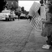 "Lyla Robison, 4, stands with her family and waves a small American flag during the annual Veterans Parade in the background on Saturday, Nov. 9, 2013, in downtown Nacogdoches. According to the Camerapaedia website, ""The FED camera was introduced in 1934 by factory of the Dzerzhinsky Commune in Kharkov, Ukraine, former USSR. FED are the initials for F.E. Dzerzhinsky, the founder of the NKVD, in honor of him the camera was named."""
