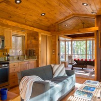 An ESCAPE tiny house living area with screened porch beyond