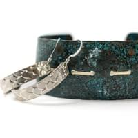 Silver Scale Half hoop earrings displayed with a Sea green Patina Copper cuff, finished with woven Spruce Root