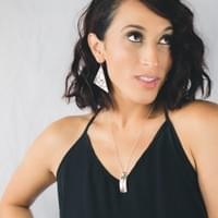 Nancy is wearing Alaska Botanical earrings, Triangle Cut paired with the two-tone love bird necklace.
