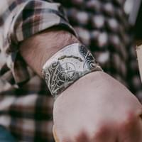 This custom cuff features a compass rose, complete with coordinates carved on the inside of the cuff.