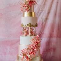 8 tier wedding cake in pink, blush, white and gold with geometric separator, edible gold leaf, mouldings and dramatic wafer paper edible petals and flowers