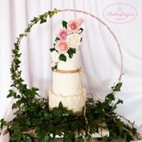 Rustic white 4 tier wedding cake with wood bark effect, rustic wall effect, texture effect on a hoop cake display, with ivy and handmade sugar flowers