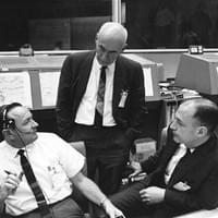 Discussing the scrub of the Gemini VI space flight are (from left), Christopher C. Kraft Jr., Red Team flight director; Dr. Robert R. Gilruth, center director; and George M. Low, deputy director.