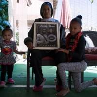 At her home in Las Vegas, Nevada, Trinita Farmer, mother of LVMPD homicide victim, Tashii Brown, poses with portraits of her son and her two granddaughters.  Tashii died after he was tased, punched, and put in an illegal chokehold while having a mental health crisis at The Venetian on Mother's Day, 2017.  March 4, 2018.  Photo by Nissa Tzun, Forced Trajectory Project.