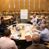 People seated at round table next to flip chart