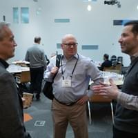 3 business men talking during a break at a conference
