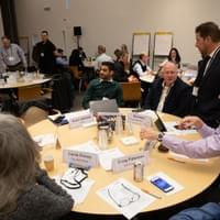 Room of business people interacting in small groups