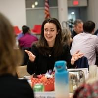 Smiling woman talking at a table during a conference