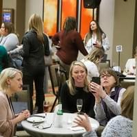 4 women sitting socializing at a cocktail table