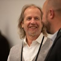 Smiling man talking with another man at a conference