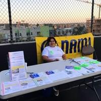 NAMI Urban LA's Spanish Program Outreach Coordinator, Rosa Alvarez, working the resource table at the Rooftop Movies event on June 8, 2018 at Immanuel Presbyterian Church.