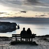Photo of a couple on a bench at Etretat, France