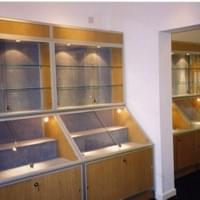 Smethwick Museum, West Midlands. Shaped base cabinets with wall cabinets above. Silver frame with fabric backs & base.  Light oak wood grain panelling.  Halogen lights.