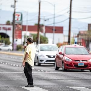 Man stands in the middle of the crosswalk and woman follows behind. Nevada. July 23, 2018. Photo by Eduardo D. Rossal.