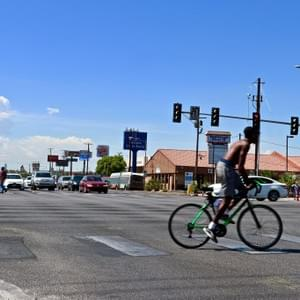 Lively shot of intersection between Maryland Parkway and Desert Inn. Man rides bike across crosswalk as traffic is stalled, Las Vegas, NV, July 26, 2018. Photo by Joshua Herrera