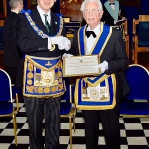 The Provincial Grand Master presents W Bro T H Coulter with a Certificate marking the 70th anniversary of his initiation