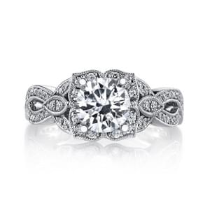 A Floral Motif Engagement Ring with Elaborate Petal Design, Peek-A-Boo Diamond Accents and Milgrain detailing. Shown in White Gold with One Carat Round Brilliant Cut Center; Price does not include center stone. Side Stones: 0.44 Carat Total Weight.