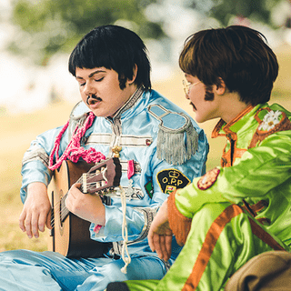 Two cosplayers as The Beatles. One playing guitar.