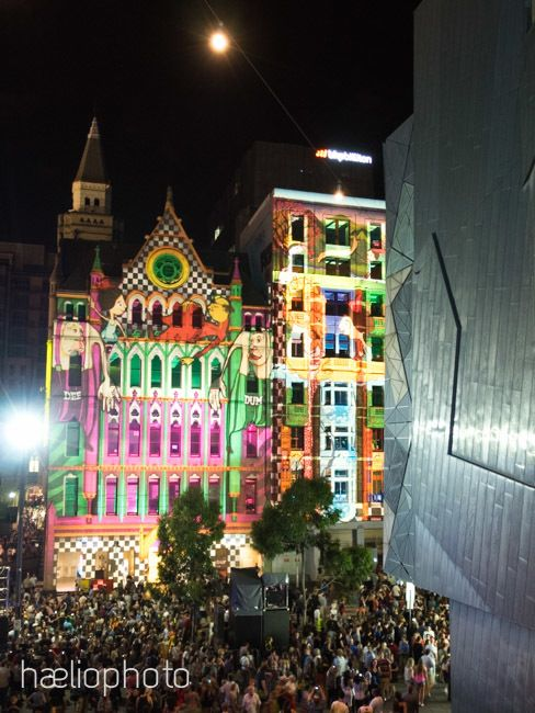 Looking from Federation Square across the crowd at the building projections along Flinders Street at White Night Festival