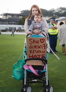 A mother at the Wellington vigil with her child and a sign that says 'She doesn't know hate'