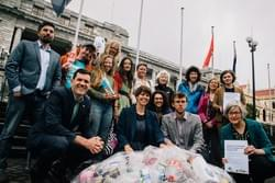 Members of the Kiwi Bottle Drive team outside Parliament with MPs and supporters, and a big net of plastic waste.
