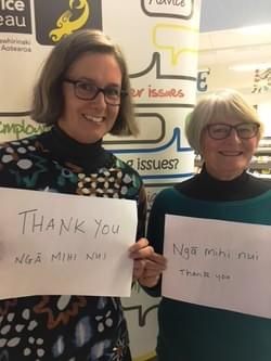 Lucy, the Wellington CAB manager, and one of the CAB's volunteers smiling and holding signs saying 'Thankyou, ngā mihi nui'