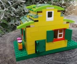Lego sculpture of a yellow house showing how to reduce carbon