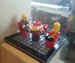 Lego sculpture of two people eating in a cafe