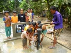 A grateful Cambodian family enjoying fresh water from a well installed by the Mark & Trina Ramsey Foundation in celebration of Trina & Lisa's father's 83rd birthday