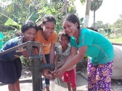 Cambodian family enjoying the water well generously donated by Mark & Trina Ramsey Foundation supporter George Ryon