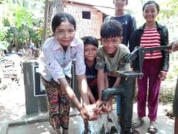 The family of Pieng Oinng  & Tub Thom enjoying water from the well in Cambodia installed by MTRF in celebration of Dave & Nancy Hoke's anniversary