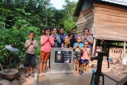 The Saun Sok  family + 3 children & The  Chhuk Po  family + two children shown with the water well in Cambodia they share.  This well was donated by the Mark & Trina Ramsey Foundation in celebration of Mark's father, Dean's 79th birthday