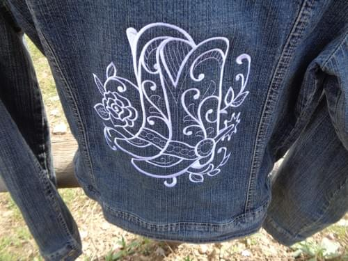 Women's jean jacket with white custom embroidery.