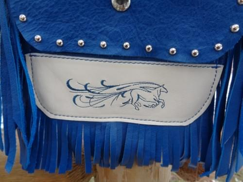 Bllue and creme hip bag with flowing horse embroidery.