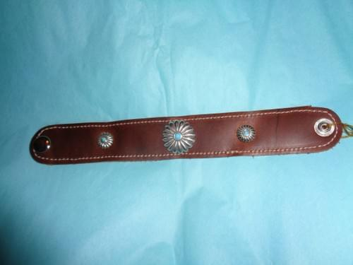 Brown leather bracelet with conchos.