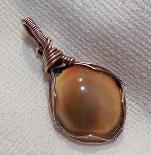 Ciondolo reversibile in Occhio di Santa Lucia e Rame