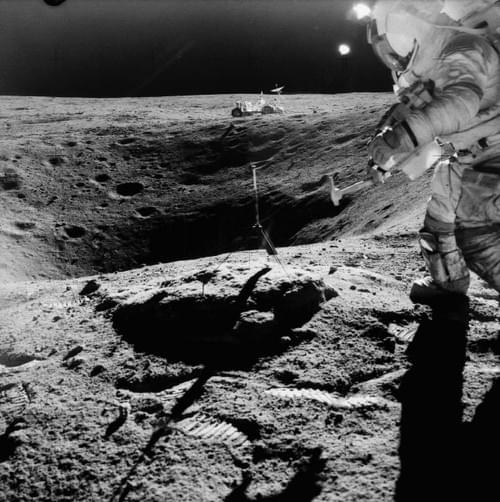 Apollo 16 Astronaut John Young on rim of Plum crater gathering lunar rock samples