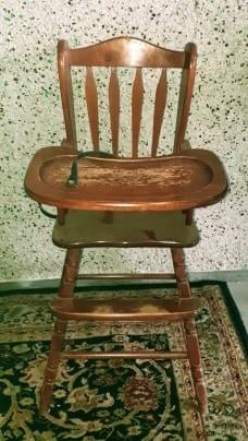 Vintage high chair with seat buckle.