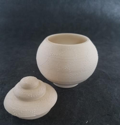 Lidded clay pot with delicate white dots pattern