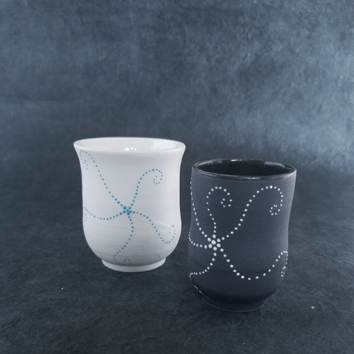 white porcelain cup with a blue star fish or black clay and white star fish