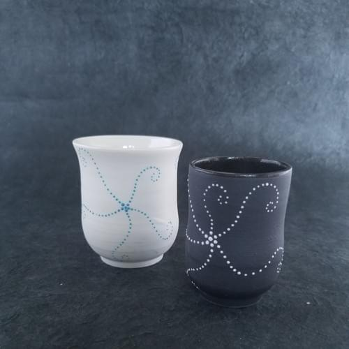 white porcelain tea cup with a blue star fish or black clay and white star fish