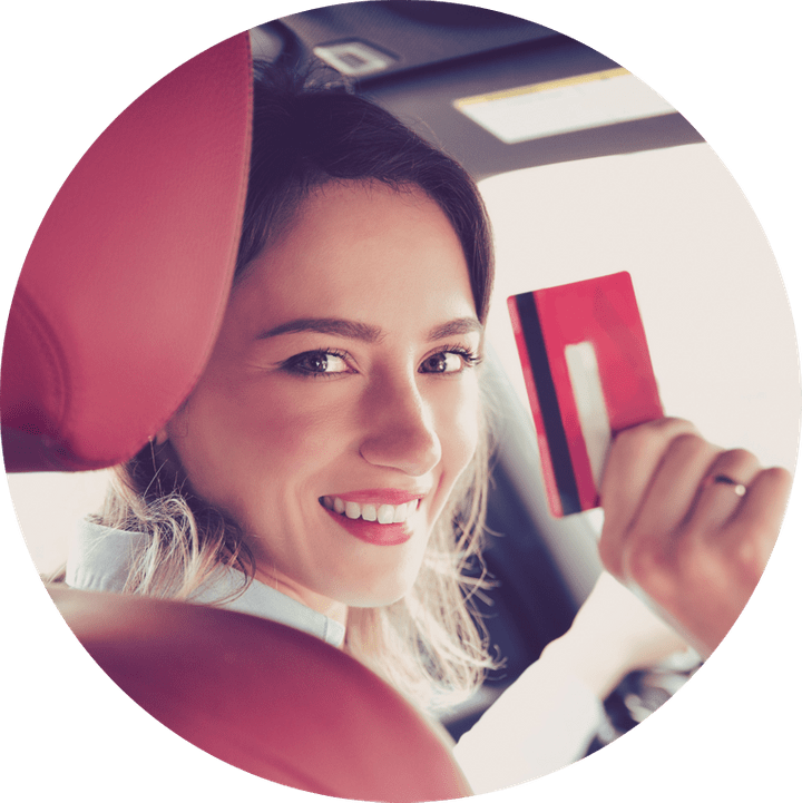 A smiling woman driving a car with a bank card in her hand