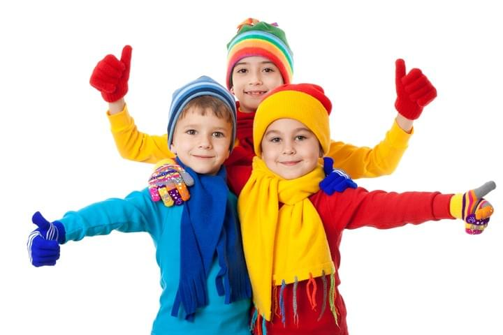 Three kids in red, yellow and blue winter clothes showing thumbs up
