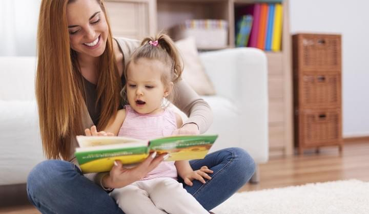 Lady enjoys ready a book to a toddler on her lap