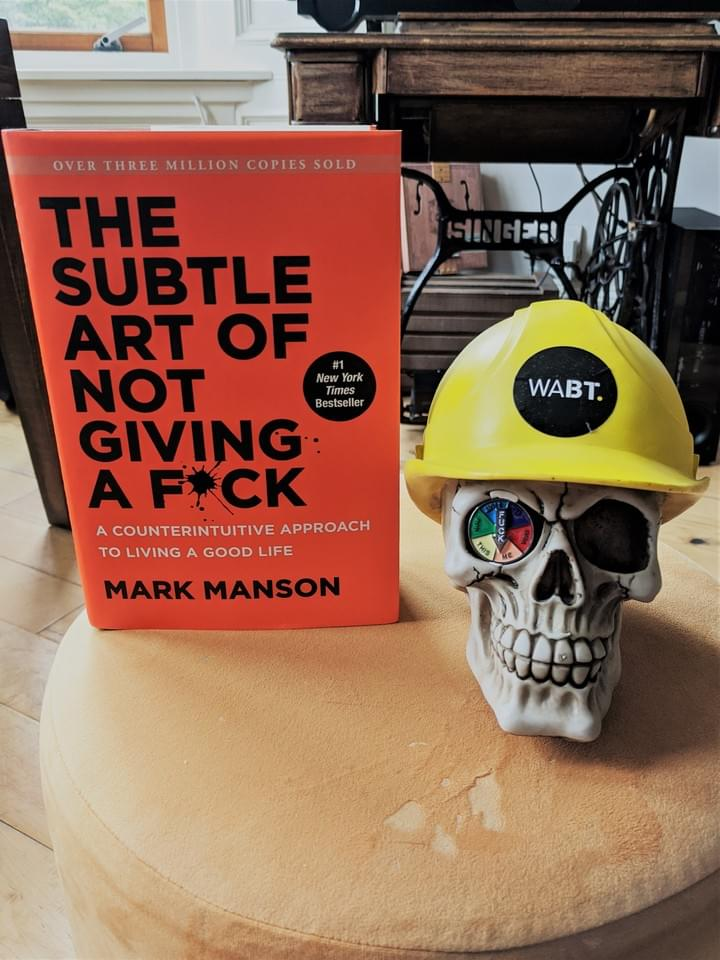 We Are Brass Tacks. Internal comms agency. Fred the Head. Book of the month. The Subtle Art of Not giving a Fuck. Skull with hard hat sitting on gold table next to an orange book
