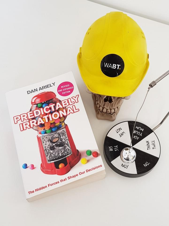 We Are Brass Tacks. Internal comms agency. Fred the Head. Book of the month. Leaders eat last. Skull with hard hat sitting beside black and white decision board and book