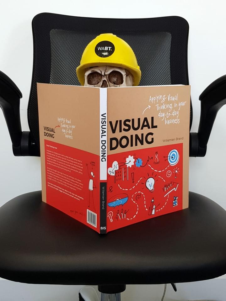 We Are Brass Tacks. Internal comms agency. Fred the Head. Book of the month. Visual Doing. Skull in yellow hard hat sitting on black office chair with a book in front.